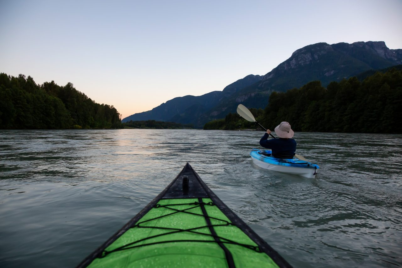 Kayaking in a river surrounded by Canadian Mountains during a vibrant summer sunset. Taken in Squamish, British Columbia, Canada.
