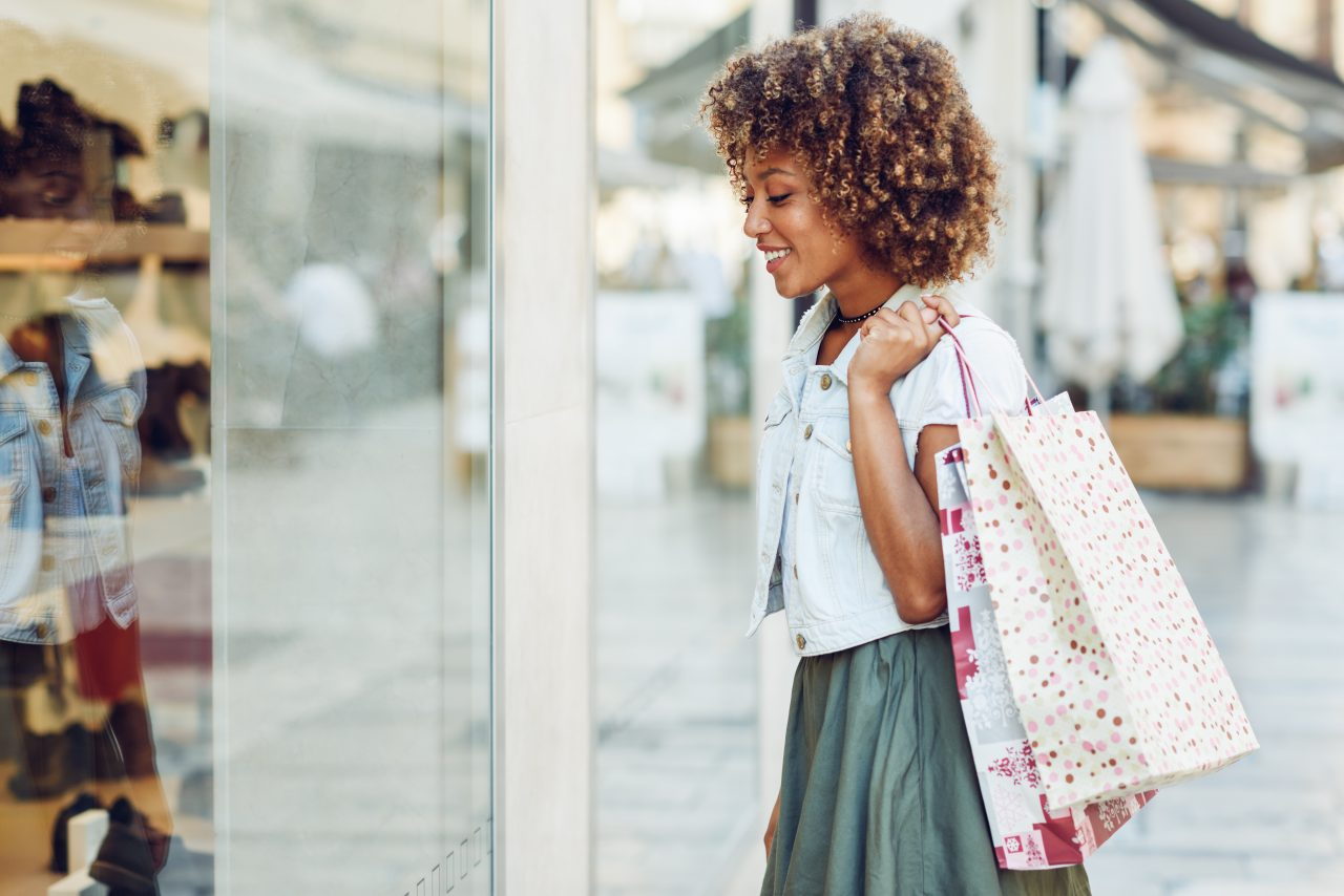 Young black woman, afro hairstyle, looking at a shop window